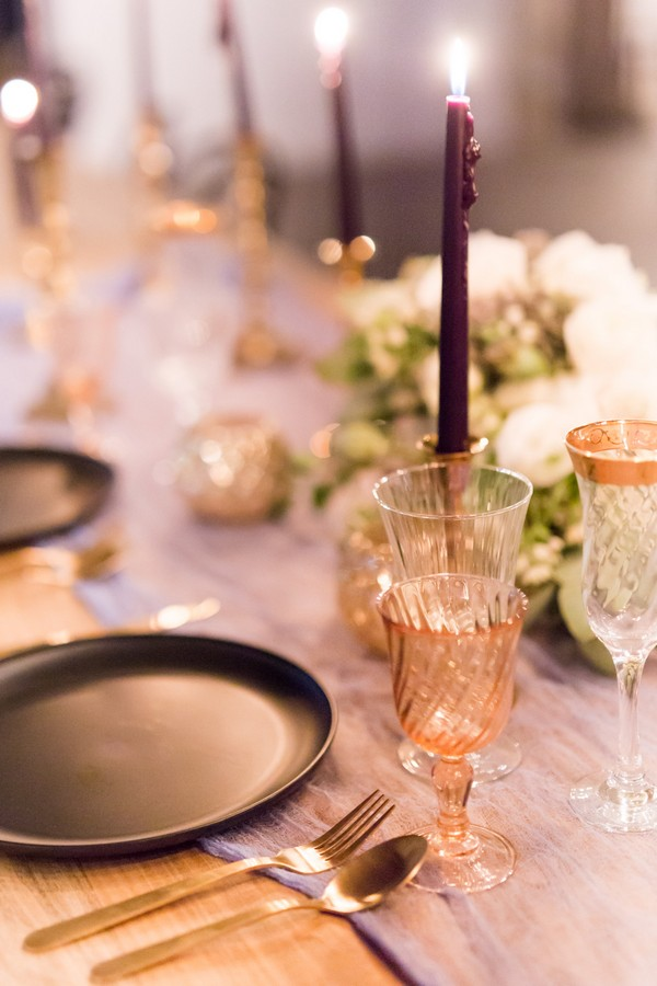 Glassware and purple candles on wedding table