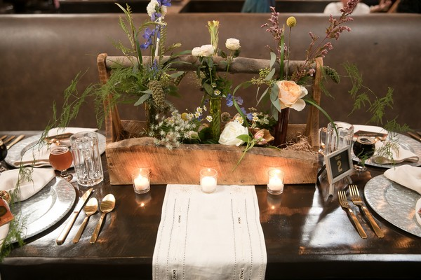 Wooden planter of wedding flowers in centre of table