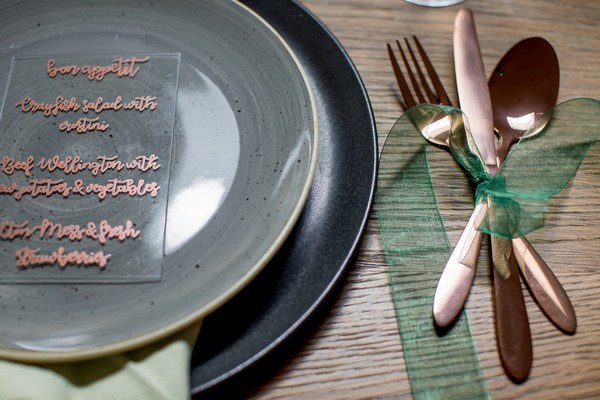 Copper cutlery wrapped in green ribbon
