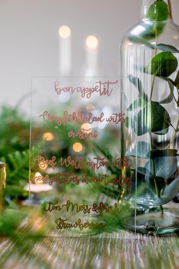Wedding menu written in gold lettering on glass