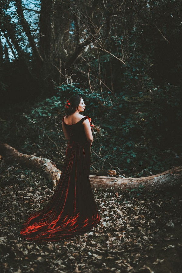 Bride wearing red velvet wedding dress in woods