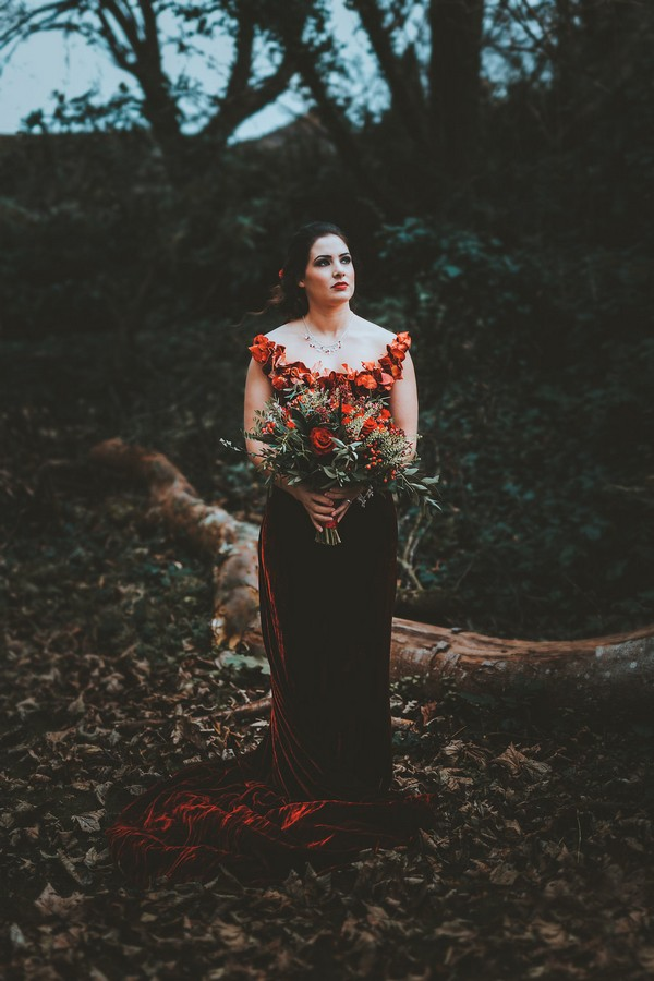 Bride with red wedding dress holding red bridal bouquet