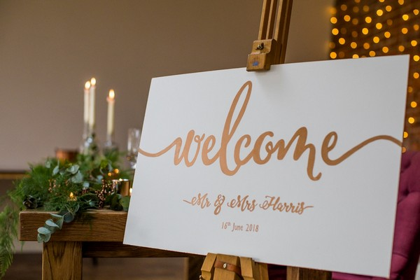 Copper wedding welcome sign on easel