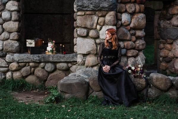 Gothic bride sitting on rocks by castle