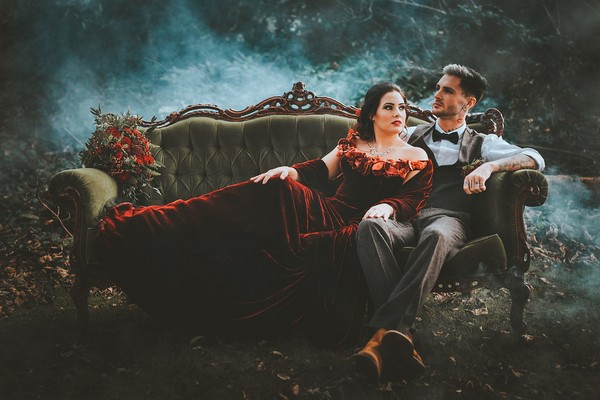 Bride and groom sitting on couch in woodland