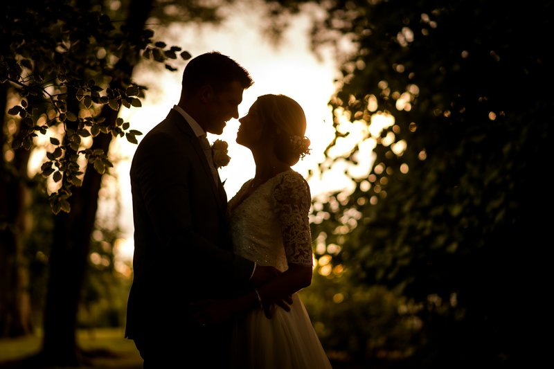 Bride and groom facing each other as light shines through trees behind them