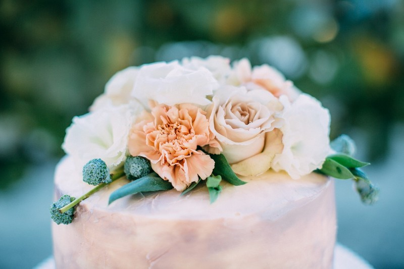 Flowers on top of soft mauve coloured wedding cake