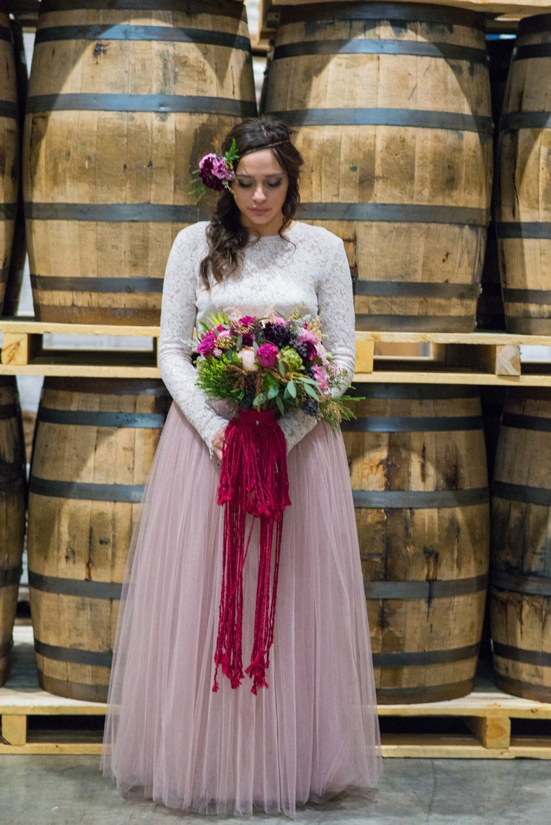 Bride holding bouquet in front of barrels at Breckenridge Distillery