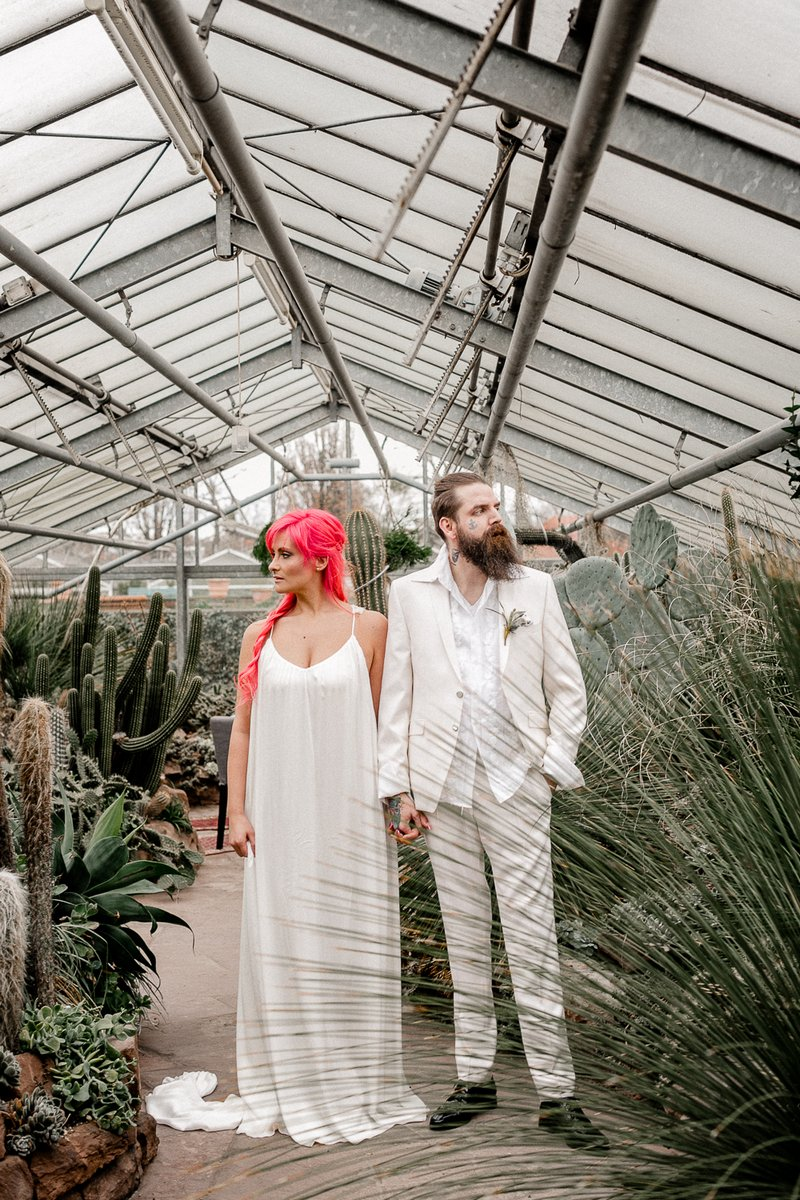 Bride with pink hair holding hands with groom in white suit