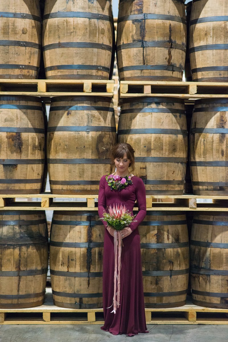 Bridesmaid in purple dress standing in front of barrels at Breckenridge Distillery
