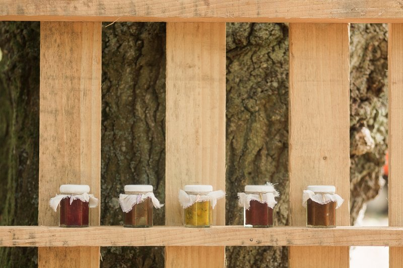 Small jars of preserves on wooden pallet