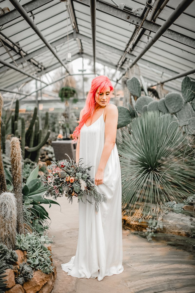 Bride holding bouquet in greenhouse full of cactuses