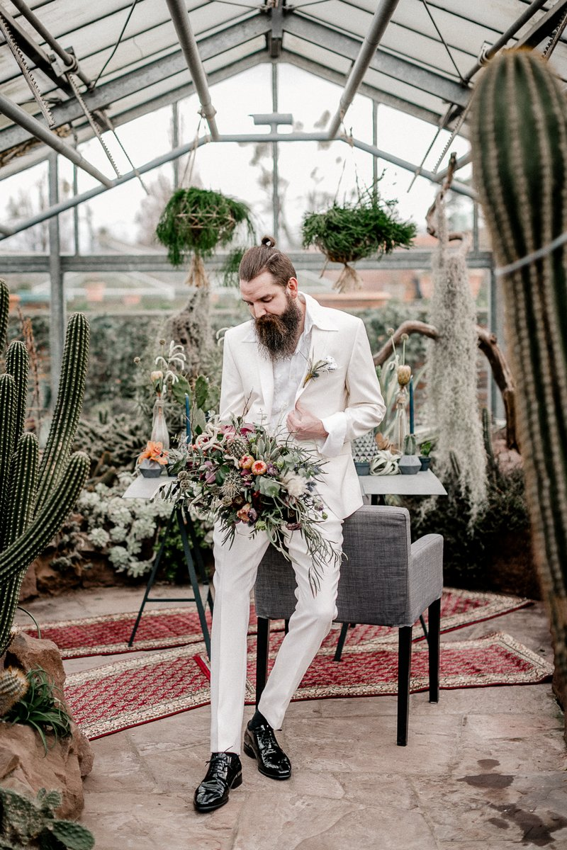 Groom in white suit holding bouquet