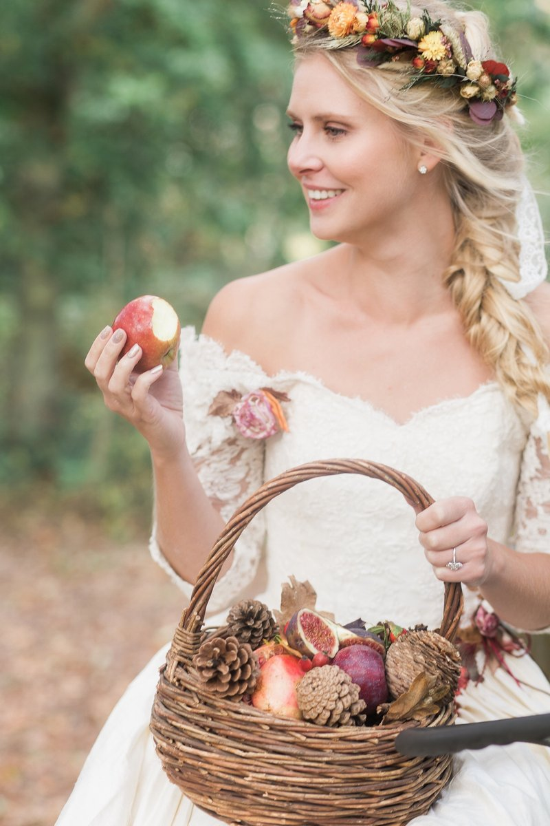 Bride holding apple and basket of fruit