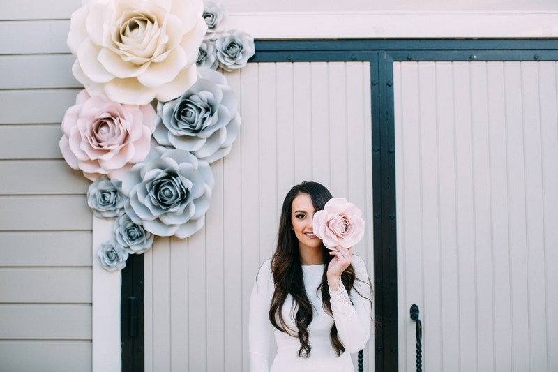 Bride standing by paper flower backdrop
