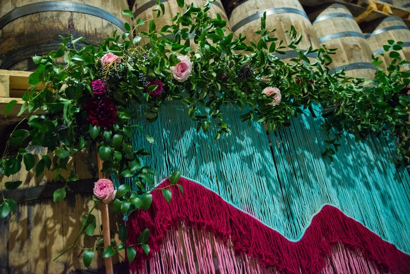 Wedding ceremony backdrop of coloured tassels and flowers