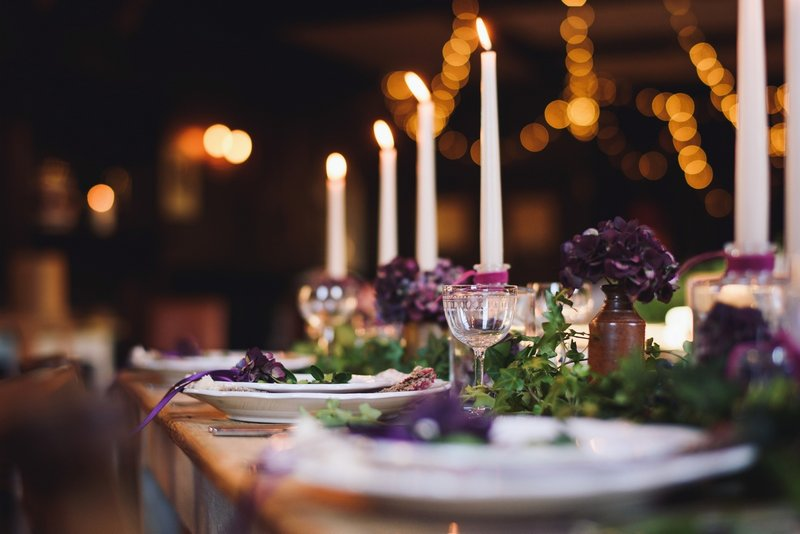 Candles and plates on rustic table to create hygge wedding styling