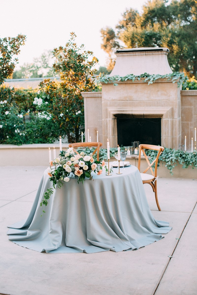 Small wedding table with dusty blue tablecloth and pastel wedding flowers