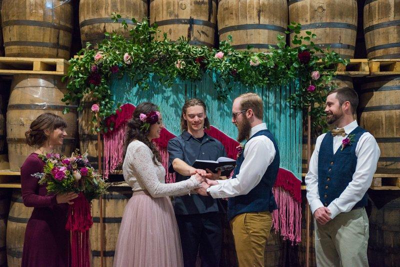 Wedding ceremony in front of barrels at Breckenridge Distillery