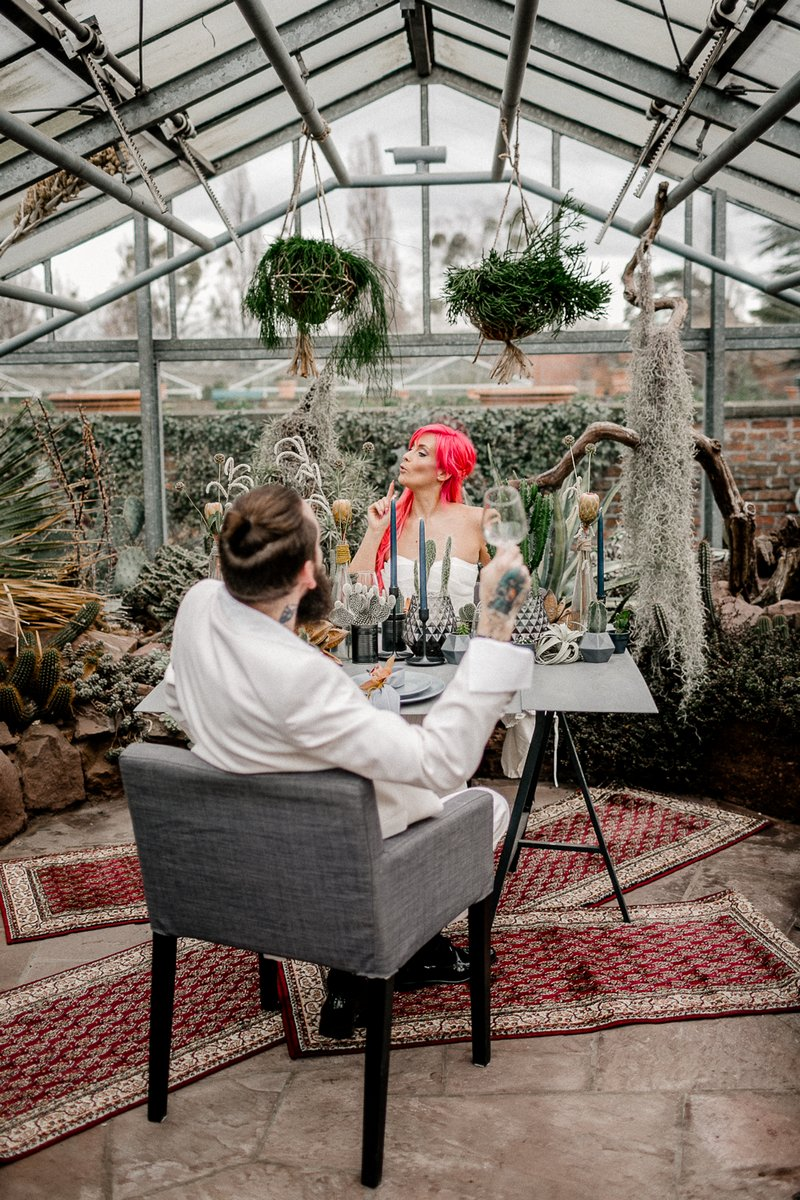 Bride and groom sitting at wedding table in greenhouse