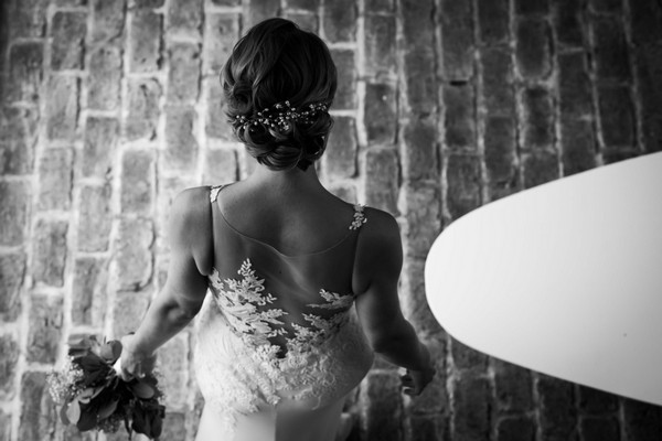 Back of bride as she walks over brick floor - Picture by Carine Bea
