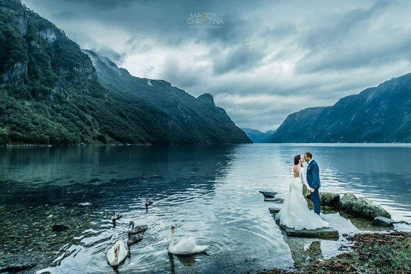 Bride and groom standing by lake surrounded by mountains - Picture by Maddy Christina Photography