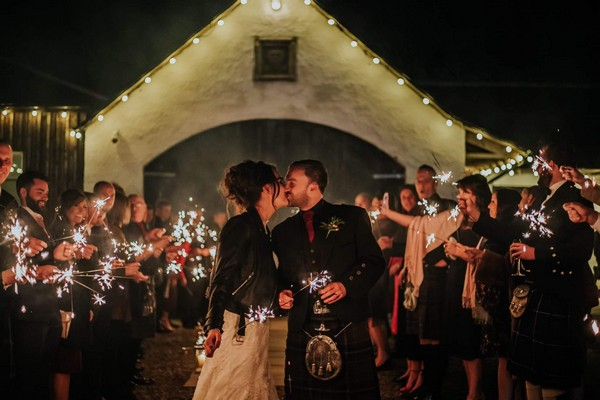 Bride in leather jacket kissing groom in kilt surrounded by guests with sparklers - Picture by Rebecca Rose Noller Photography