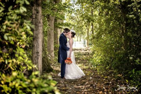 Bride and groom kissing by trees in woodland - Picture by John Young Photography