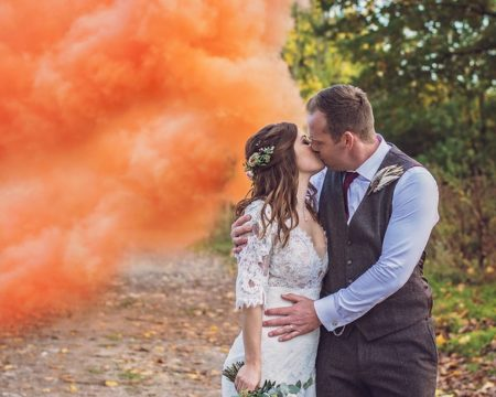 Bride and groom kising next to orange smoke - Picture by Rebecca Gurden Photography