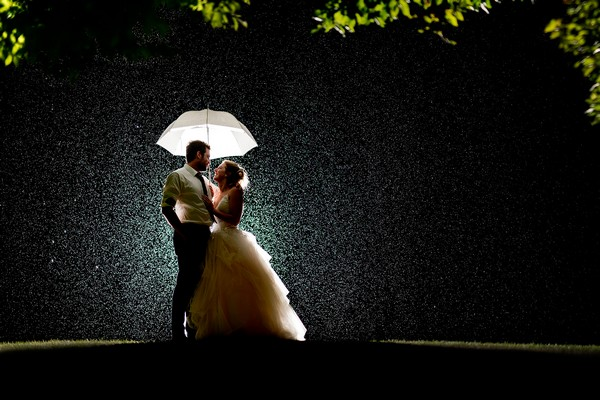 Bride and groom standing under umbrella in the rain at night - Picture by Matt Selby Photography
