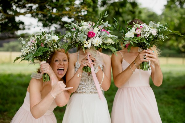 Bridesmaid doing hang loose shaka hand gesture next to bride and bridesmaid with bouquets over their faces - Picture by Voyteck Photography