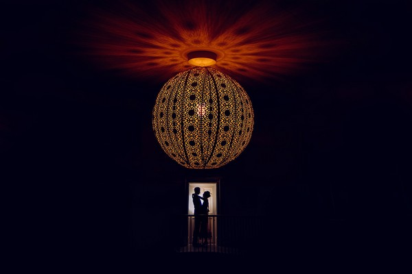 Silhouette of bride and groom under beautiful light fitting - Picture by Fiona Walsh Photography