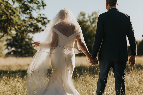 back view of bride and groom as they walk through field - Picture by BGS Weddings