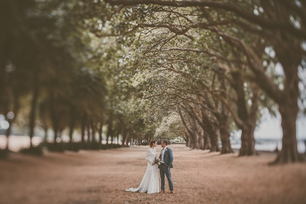 Bride and groom standing under line of trees - Picture by Michelle Lindsell Photography