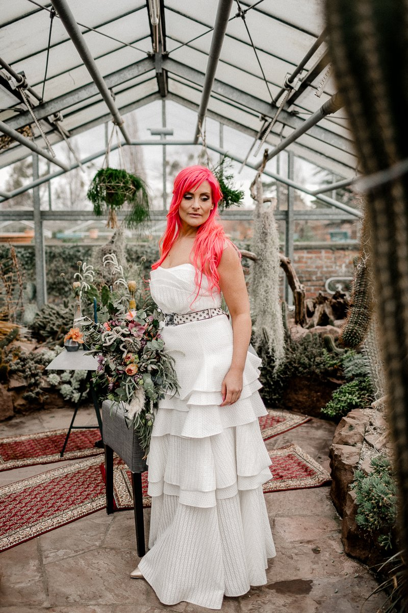 Bride with pink hair wearing wedding dress with ruffle layered skirt