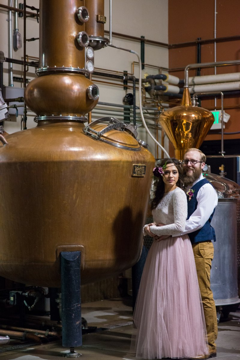 Bride and groom in front of distillery equipment