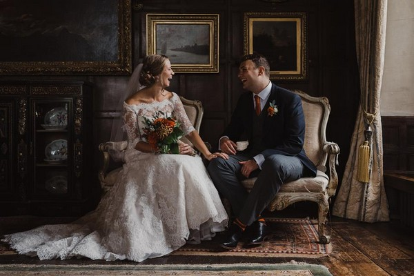 Bride and groom sitting in chairs laughing - Picture by Will Patrick Wedding Photography