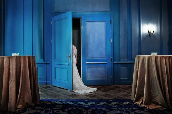 Bride leaving room through blue door - Picture by Franck Boutonnet Photography