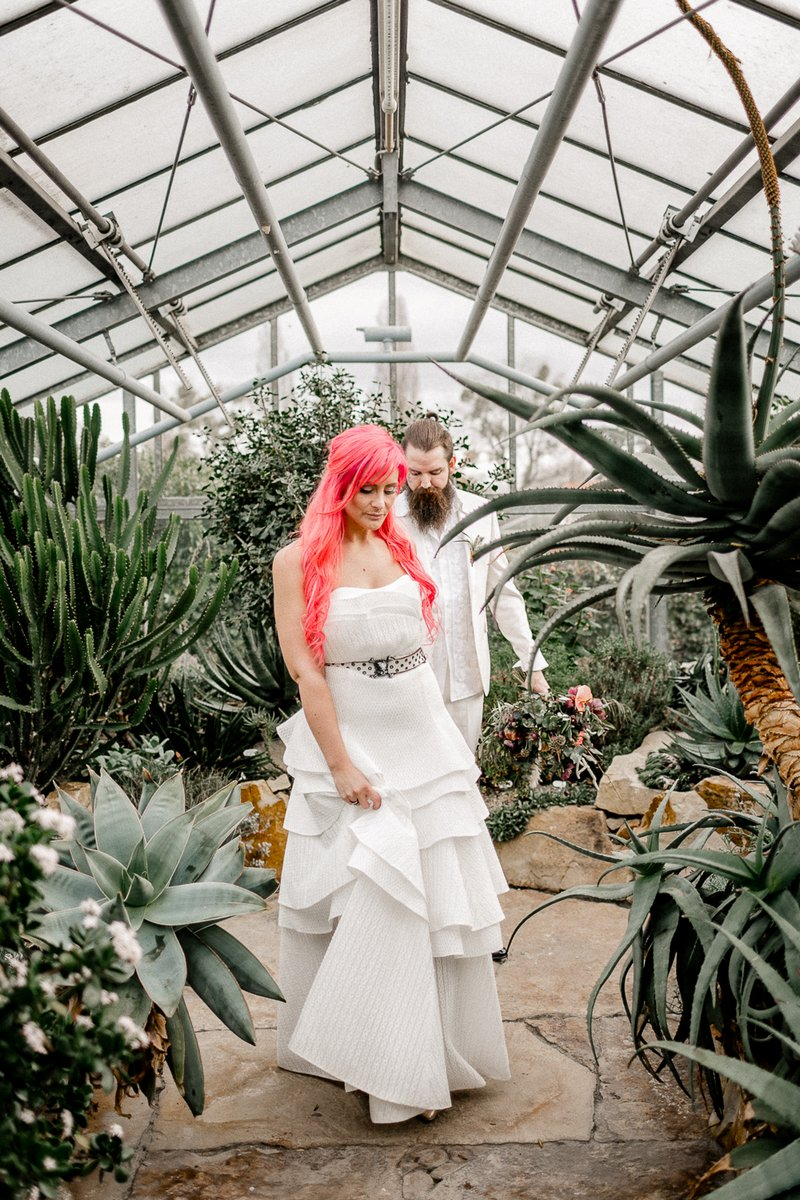 Bride leading groom by the hand through greenhouse full of cactuses