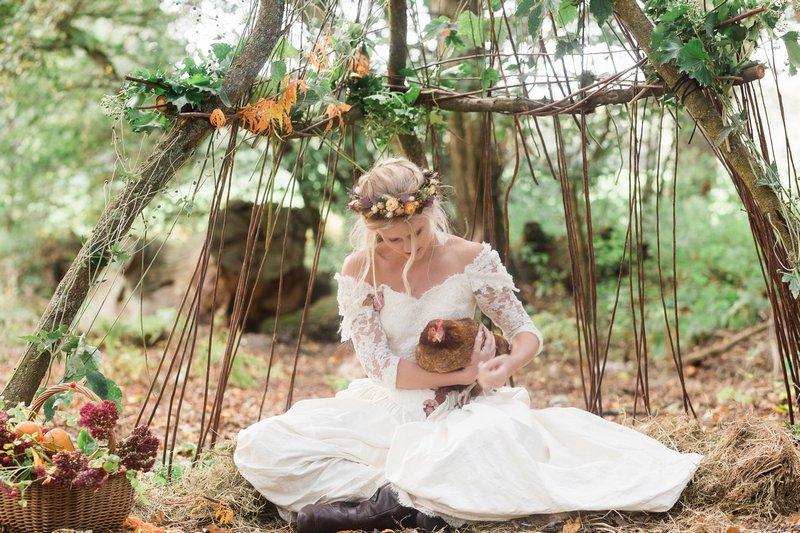 Bride sitting in woodland holding chicken
