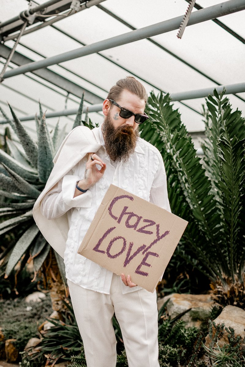 Groom with sunglasses holding sign saying Crazy Love