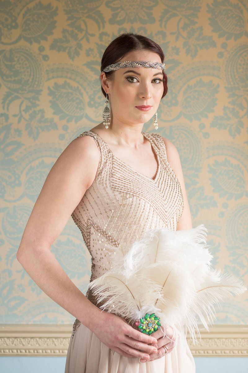 Bridesmaid wearing mink dress and vintage style headband holding feathers