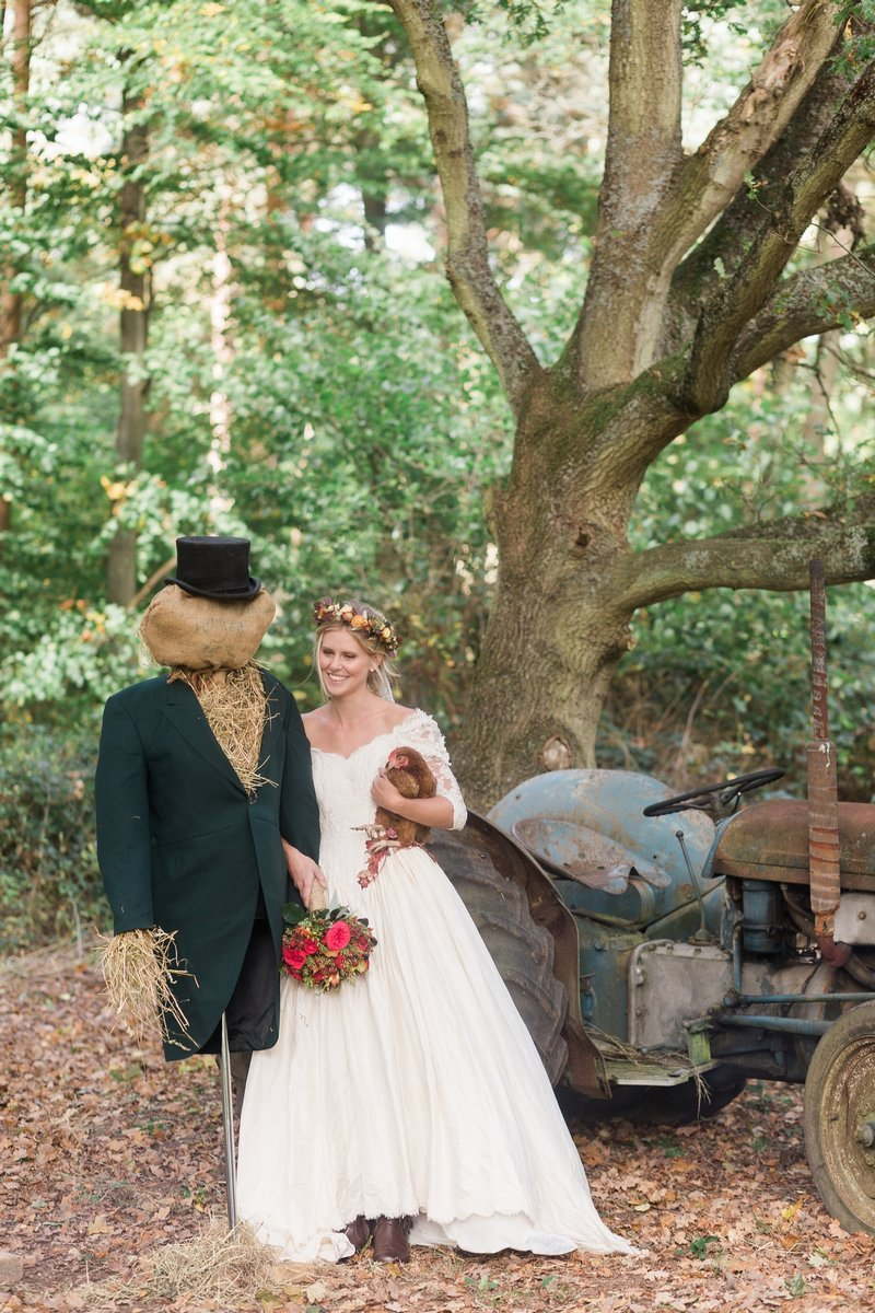 Bride standing in woodland next to groom scarecrow