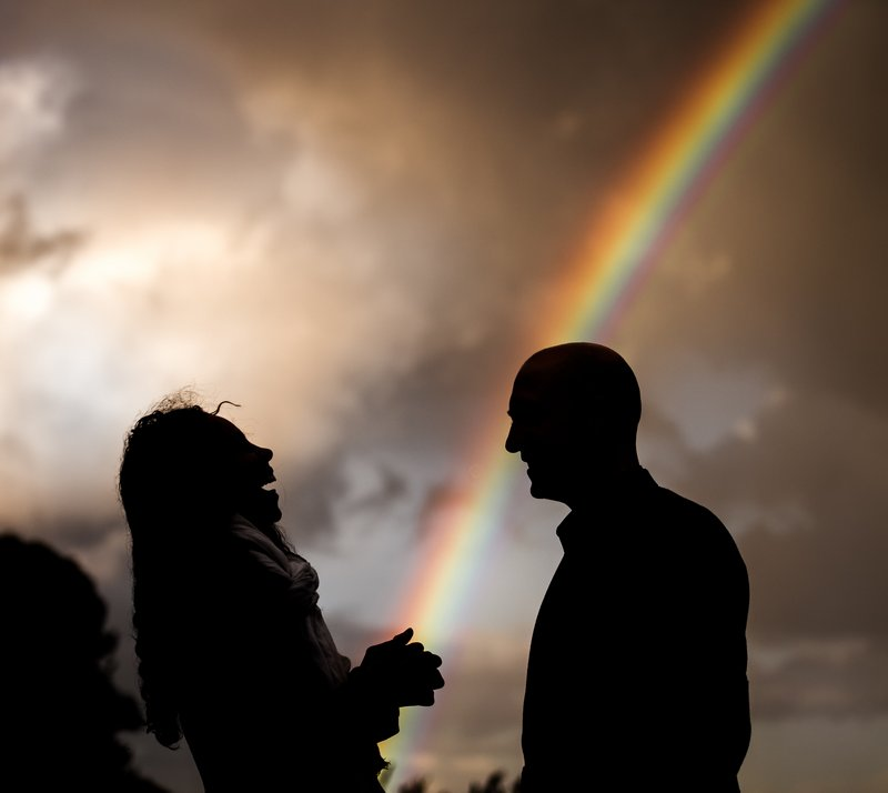 Silhouette of wedding guests talking with rainbow in background
