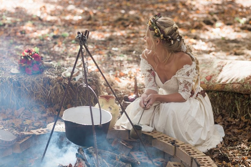 Bride crouching by open fire in woodland