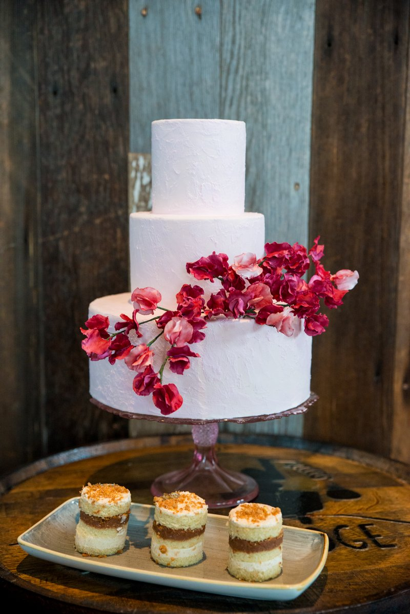 Plain white wedding cake decorated with red flowers