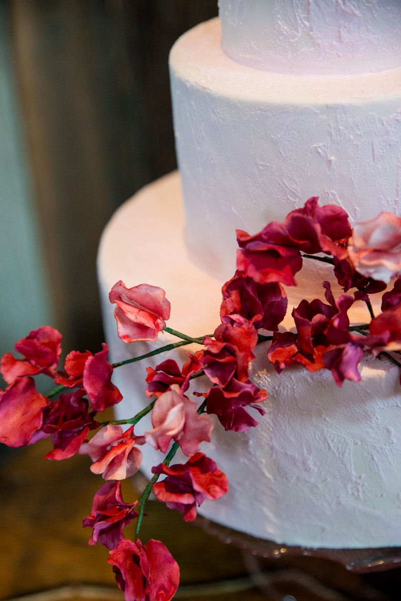 Red flowers on plain white wedding cake