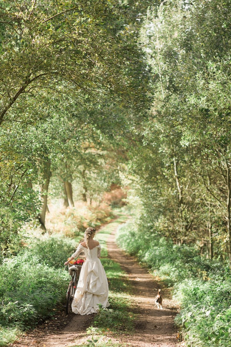 Bride walking through woodland with bicycle