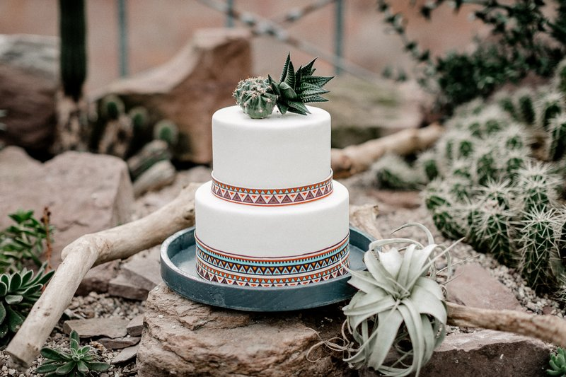 White wedding cake with cactus topper