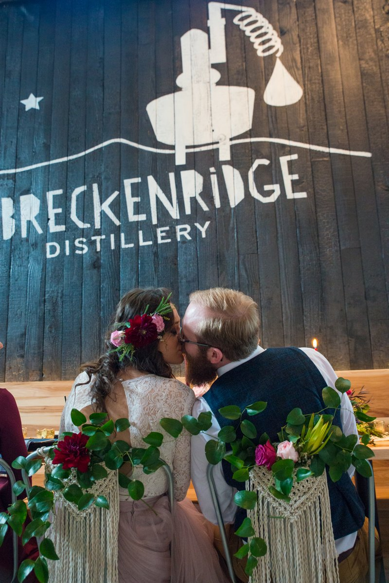 Bride and groom kissing in front of Breckenridge Distillery sign
